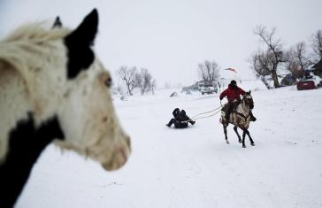 In this Tuesday, Nov. 29, 2016 photo, Smokey, a member of the Sioux Native American tribe, rides the horse Prophecy, a descendant of the horse belonging to war chief Crazy Horse, as he pulls a sled at the Oceti Sakowin camp where people have gathered to protest the Dakota Access oil pipeline, in Cannon Ball, N.D. The government has ordered protesters to leave federal land by Monday, but they insist they will stay for as long it takes to divert the $3.8 billion pipeline. (ANSA/AP Photo/David Goldman) [CopyrightNotice: Copyright 2016 The Associated Press. All rights reserved.]